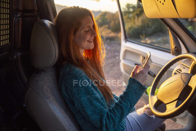 Young woman on a road trip, using smartphone — Photo de stock