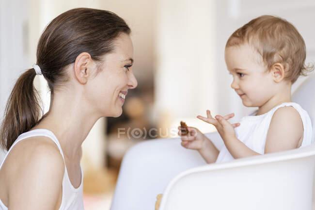 Профиль счастливой матери, наблюдающей за своей маленькой дочерью — стоковое фото