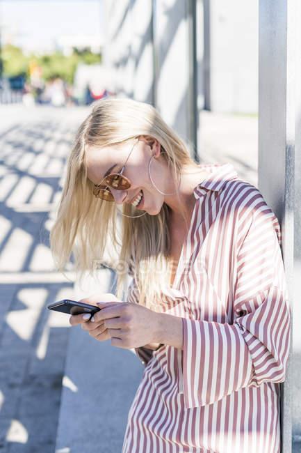 Mujer joven rubia usando teléfono inteligente al aire libre - foto de stock