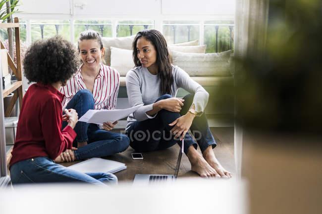 Trois femmes avec ordinateur portable et des documents assis sur le sol à la maison — Photo de stock