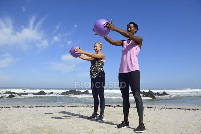 Две женщины занимаются фитнесом с мячом на пляже — стоковое фото