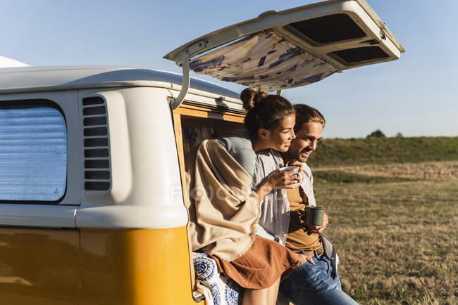 Щаслива пара робить дорогу поїздку з їх кемпер, сидячи на ліжку, пити каву — стокове фото
