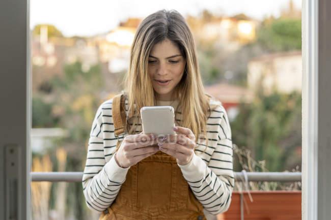 Portrait de jeune femme debout sur le balcon regardant le téléphone cellulaire — Photo de stock
