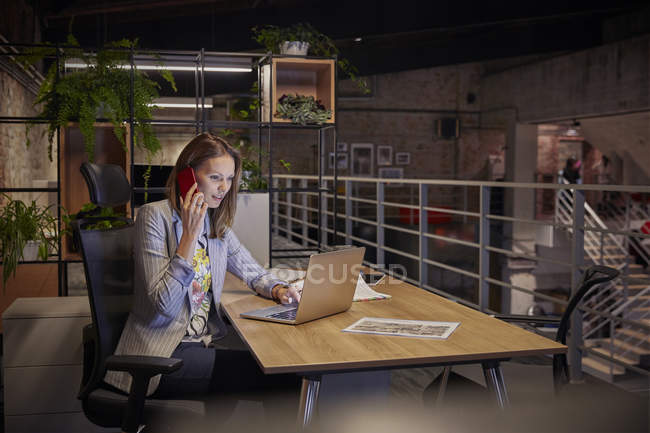 Businesswoman working in modern office, using laptop and phone — Stock Photo