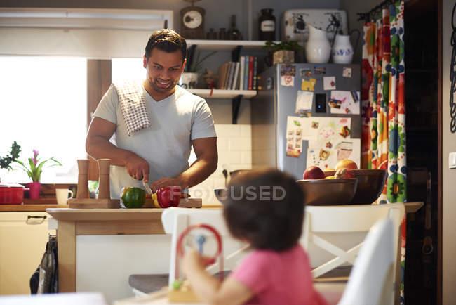 Sorrindo pai preparando comida para sua filha na cozinha em casa — Fotografia de Stock