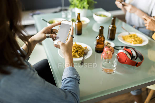 Gros plan d'amis assis à une table à l'aide d'un téléphone cellulaire — Photo de stock