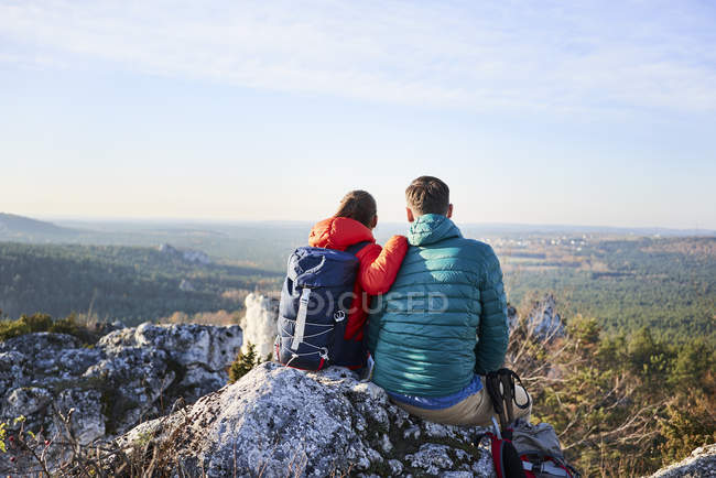 Couple sitting on rock and enjoying the view on a hiking trip in the mountains — Stock Photo