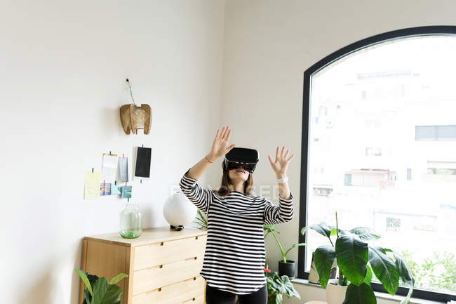 Young woman at home wearing VR glasses — Stock Photo