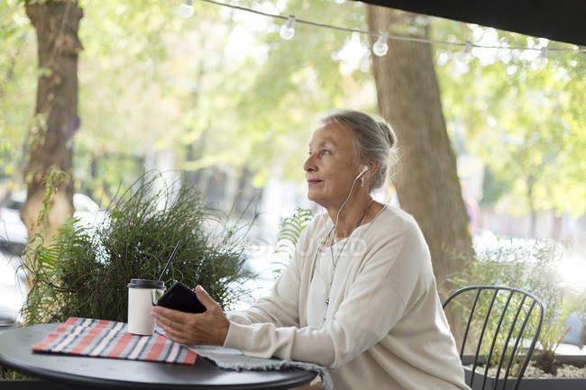 Femme âgée dans un café extérieur avec téléphone cellulaire et écouteurs — Photo de stock