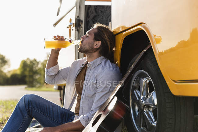 Young man on a road trip with her camper, taking a break, drinking juice — Stock Photo
