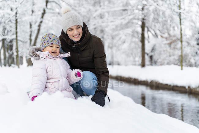 Щаслива мати з донькою на росі в зимовому ландшафті. — стокове фото
