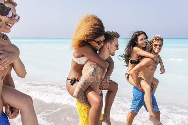Друзья, гуляющие по пляжу, несущие подружек на спине — стоковое фото
