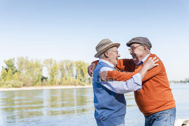 Two old friends reuniting at the riverside, embracing each other happily — Stock Photo