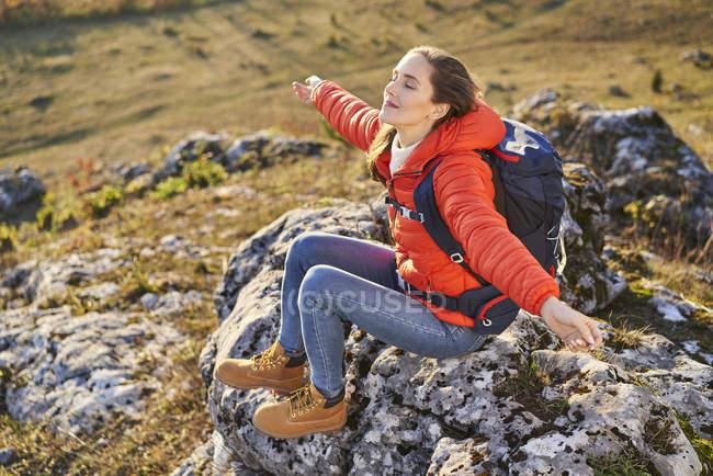 Mujer en un viaje de senderismo por las montañas descansando en una roca. - foto de stock