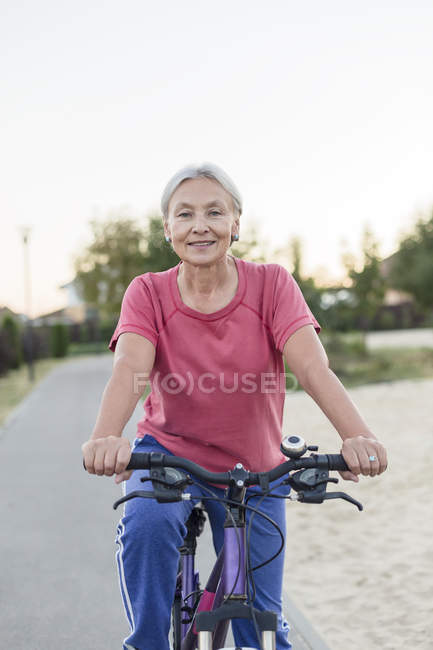 Portrait of smiling senior woman riding bicycle — Stock Photo