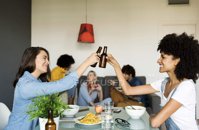 Smiling friends clinking beer bottles at dining table — Stock Photo