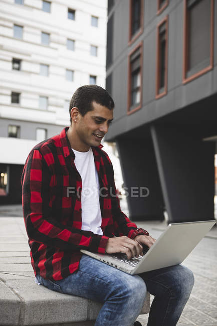Young man sitting outdoors in the city using laptop — Stock Photo