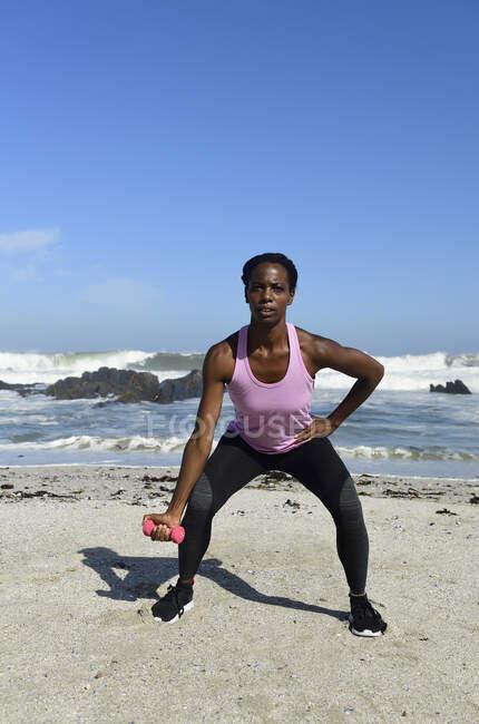 Женщина занимается фитнесом с гантелями на пляже — стоковое фото