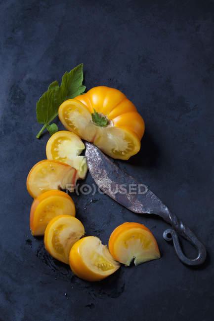 Tomate Azoychka cortado y un cuchillo viejo en terreno oscuro - foto de stock