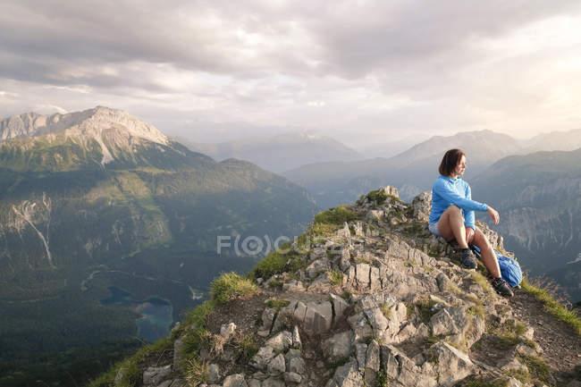 Áustria, Tirol, mulher em uma viagem de caminhada nas montanhas sentado no pico — Fotografia de Stock