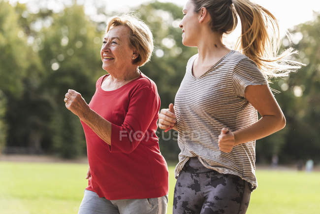 Granddaughter and grandmother having fun, jogging together in the park — стоковое фото