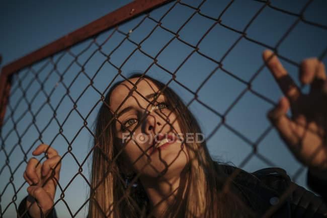 Retrato de jovem mulher atrás de cerca de malha de arame — Fotografia de Stock