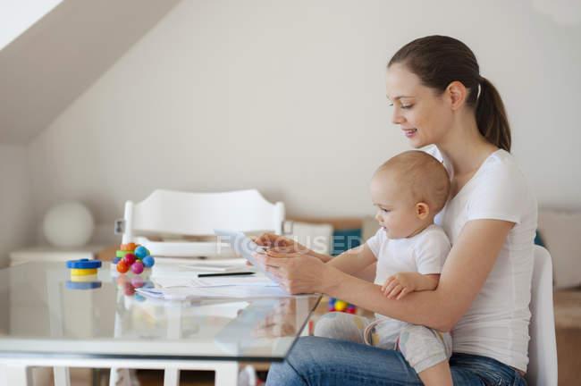 Mutter und kleine Tochter nutzen gemeinsam Tablet zu Hause — Stockfoto