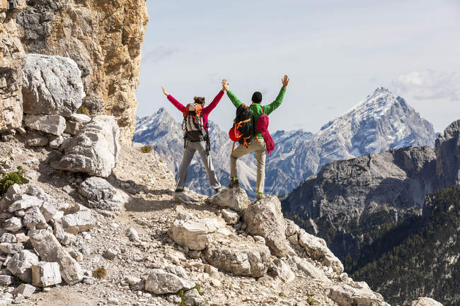 Italy, Cortina d'Ampezzo, couple with rope and climbing equipment looking at view with raised arms — Stock Photo