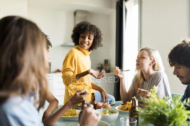 Amis assis à table parlant, mangeant et buvant de la bière — Photo de stock