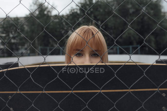 Portrait of young woman behind carver skateboard and wire mesh fence — Stock Photo