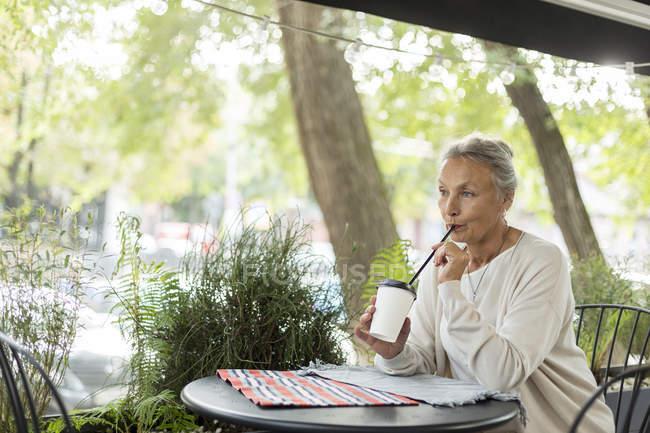 Старшая женщина с напитком в кафе на открытом воздухе — стоковое фото