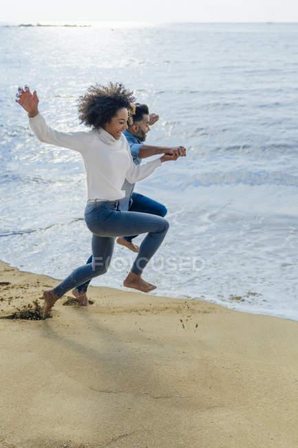 Spain, Barcelona, happy couple having fun on the beach — Stock Photo