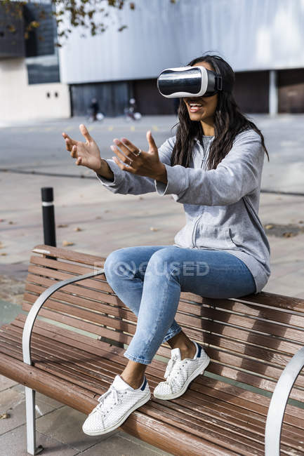 Young woman sitting on a bench, using VR goggles, reaching out with her hands — Stock Photo