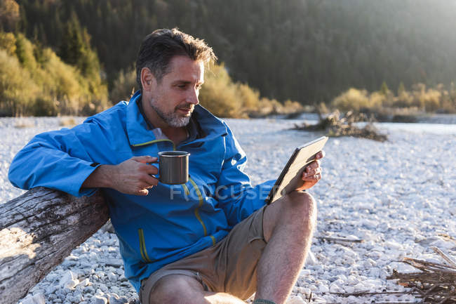 Mature man camping at riverside, using tablet — Foto stock