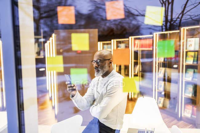 Бизнесмен за стеклом с клейкими записками смотрит на мобильный телефон — стоковое фото