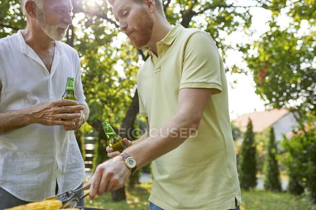 Senior padre e figlio adulto che hanno un barbecue in giardino — Foto stock