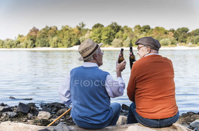 Old friends sitting by the riverside, drinking beer — Stock Photo