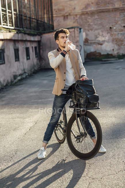 Jeune homme avec vélo fixie banlieue faire une pause sur une cour dans la ville — Photo de stock