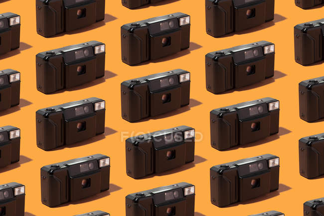 Plastic photo cameras organized in a row over orange background — Stock Photo