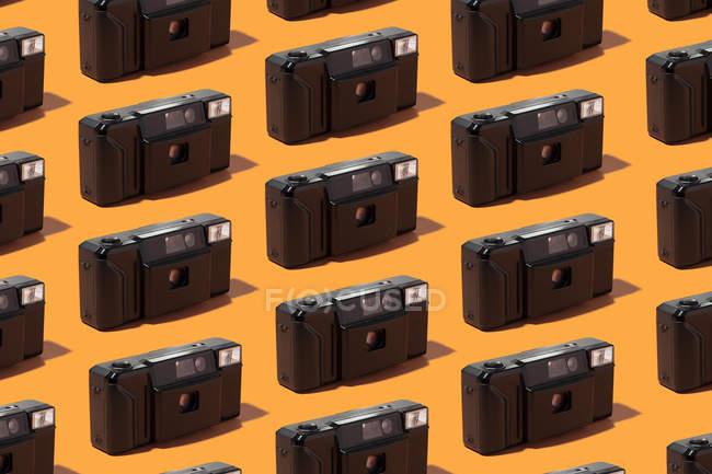 Plastic photo cameras organized in a row over orange background — стокове фото