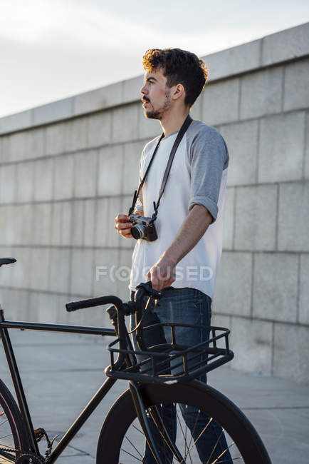 Young man with commuter fixie bike and camera looking around — Stock Photo
