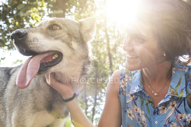Sorridente giovane donna accarezzando il suo cane alla retroilluminazione — Foto stock