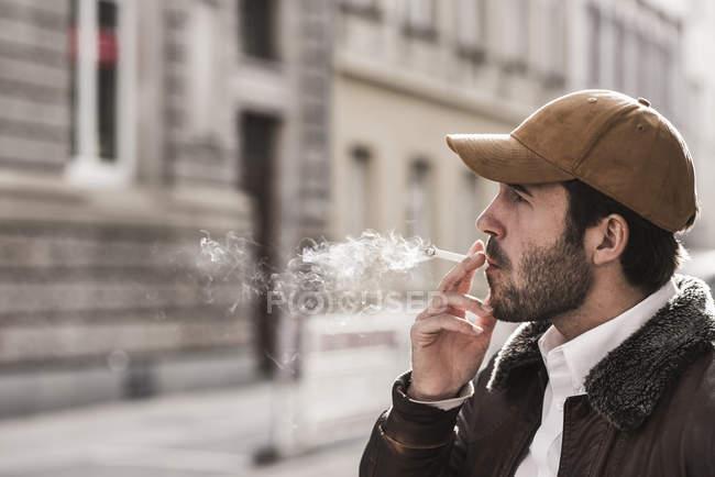 Verticale de jeune homme avec la cigarette de tabagisme de chapeau de base-ball — Photo de stock
