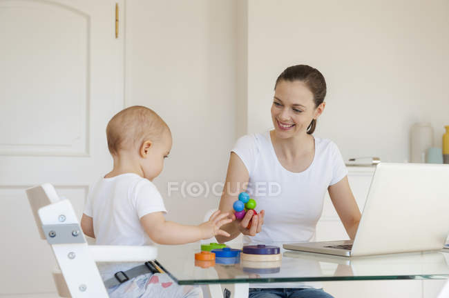 Smiling mother using laptop playing with little daughter at table at home — Stock Photo