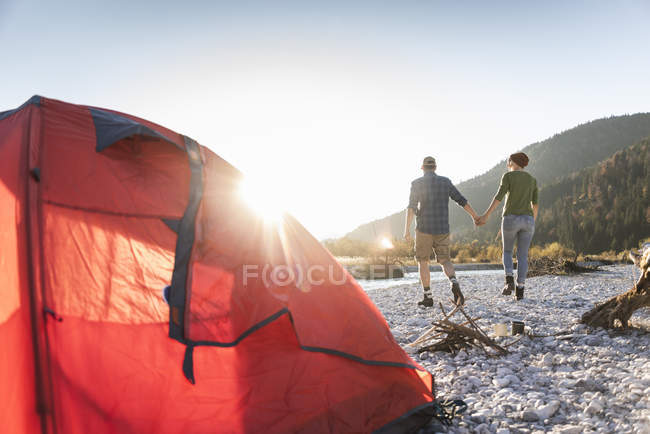 Mature couple camping at riverside in the evening light — Foto stock