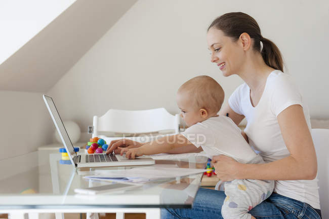 Smiling mother and little daughter using laptop together at table at home — Stock Photo