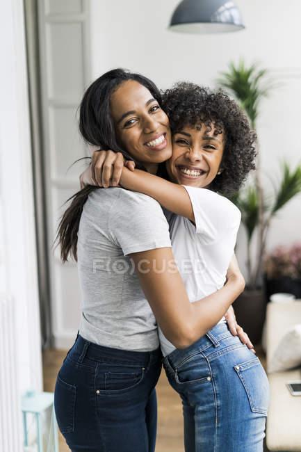 Портрет двох щасливих дівчат, які обіймаються вдома. — стокове фото
