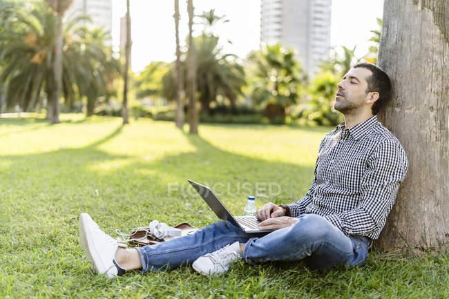 Mann lehnt mit Laptop an Baumstamm auf Wiese im Stadtpark — Stockfoto