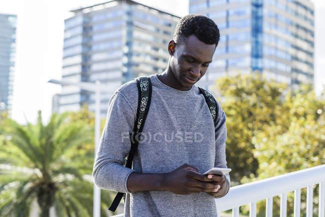 Jovem de pé em uma ponte, usando smartphone — Fotografia de Stock