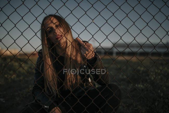 Портрет молодой женщины, сидящей за проволочной сеткой, показывающей палец — стоковое фото